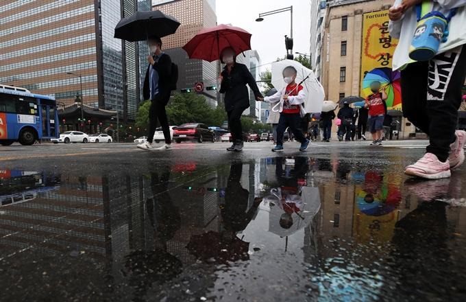금요일(28일)은 돌풍, 천둥·번개를 동반한 비가 전국적으로 내린다. 사진은 지난 27일 오전 서울 종로구 광화문 네거리에서 우산을 쓴 채 이동하는 시민들의 모습. /사진=뉴스1