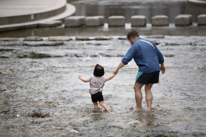 일요일인 30일 낮에는 기온이 25도 이상으로 오르는 등 대체로 맑다가 밤부터 흐려져 서해안에는 비가 내릴 전망이다. 사진은 서울 청계천을 찾은 한 어린이가 더위를 식히는 모습./사진=뉴스1