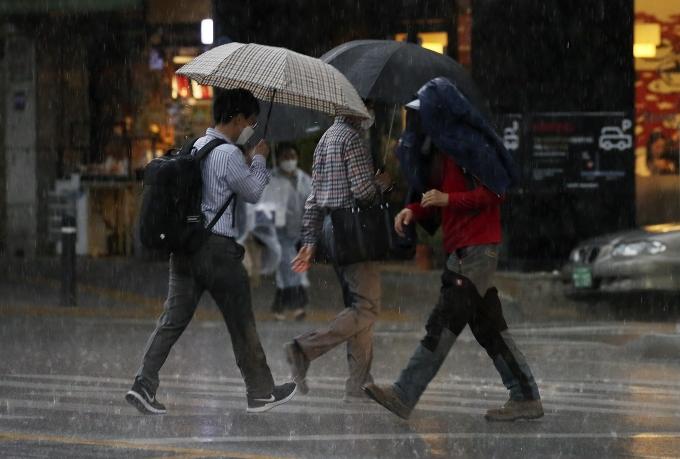 지난 28일 오후 울산 남구 한 거리에서 갑작스러운 비가 내리자 한 시민이 겉옷을 머리 위로 쓰며 비를 피하는 모습. /사진=뉴스1