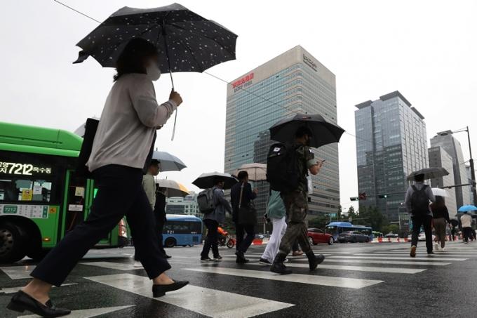 목요일(10일)은 대체로 맑은 날씨를 보이다가 밤부터 전국 곳곳에 비가 내릴 전망이다. 사진은  지난 3일 오후 서울 종로구 광화문네거리에서 우산을 쓴 채 횡단보도를 건너는 시민들의 모습. /사진=뉴스1