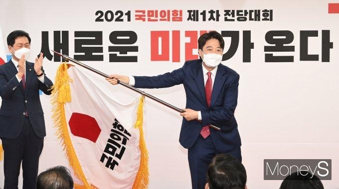[머니S포토] 국민의힘 당기 흔드는 이준석 신임 당대표