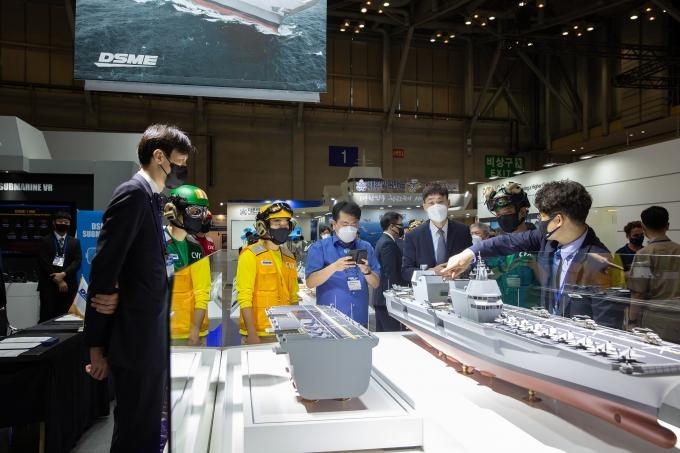 부산에서 열리고 있는 국제해양방위산업전에서 대우조선해양 홍보관을 방문한 관람객들이 한국형 경항공모함 모델을 살펴보고 있다. /사진=대우조선해양