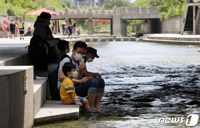서울 최고기온이 30도까지 오르며 한여름 날씨를 보인 12일 서울 청계천을 찾은 시민들, 2021.6.12/뉴스1 © News1 박세연 기자