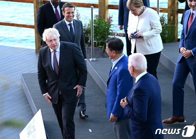 G7 정상회의 참석차 영국을 방문한 문재인 대통령(앞줄 오른쪽 두 번째)이 12일(현지시간) 영국 콘월 카비스베이 양자회담장 앞에서 기념사진을 촬영하며 보리스 존슨 영국 총리와 대화를 나누고 있다.(G7 정상회의 제공) 2021.6.13/뉴스1
