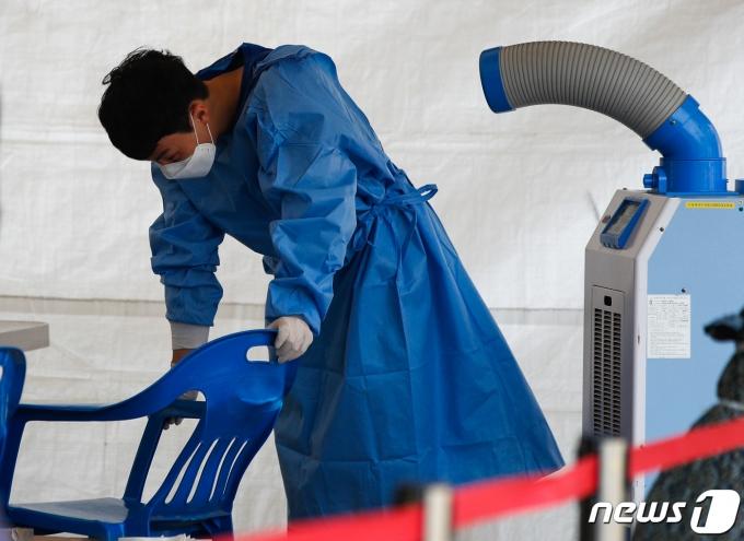 14일 서울역에 마련된 중구 임시 선별검사소에서 더위에 지친 관계자가 냉풍기 바람을 쐬고 있다. 2021.6.14/뉴스1 © News1 안은나 기자