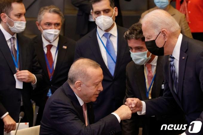 14일(현지시간) 북대서양조약기구(나토) 정상회의에서 만난 조 바이든 미국 대통령과 레제프 타이이프 에르도안 터키 대통령이 주먹인사를 나누고 있다. © AFP=뉴스1
