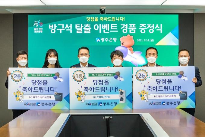 송종욱 광주은행장(왼쪽3번째)은 지난 14일 광주 동구 본점에서 '방구석 탈출 도장찍기' 이벤트1.2등 당첨자를 초청해 경품을 전달했다/사진=광주은행 제공.