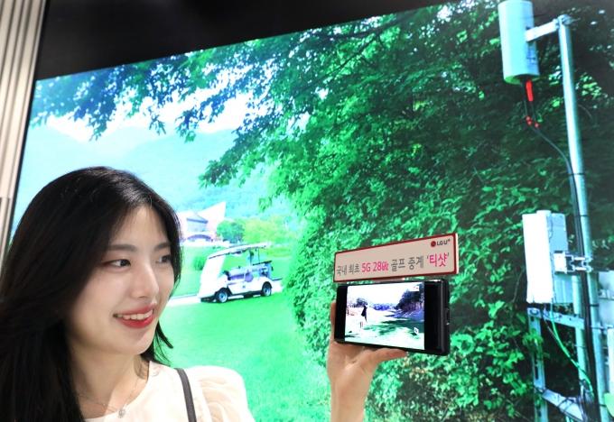 LG유플러스 모델이 레인보우힐스CC에 구축된 5G 28㎓ 기지국 현장 사진을 배경으로 U+골프 서비스를 감상하는 모습. /사진제공=LGU+