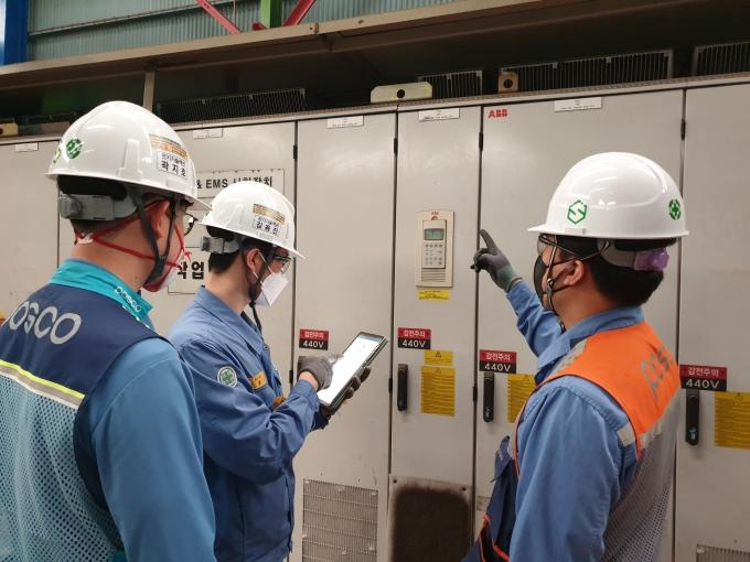 포스코 설비관리 담당 직원들이 드라이브(Drive) 패널 앞에서 태블릿으로 포인트(POINT) 시스템에 접속해 이상 조치 방법을 학습하고 있다. /사진=포스코