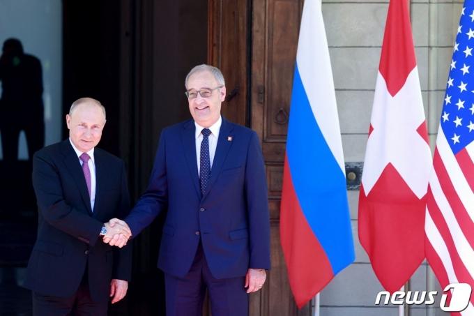 블라디미르 푸틴 러시아 대통령이 2021년 6월 16일 조 바이든 미국 대통령과의 정상회담이 열리는 스위스 제네바에 도착해 가이 파멜린 스위스 대통령과 악수하는 모습. © AFP=뉴스1 © News1 최서윤 기자