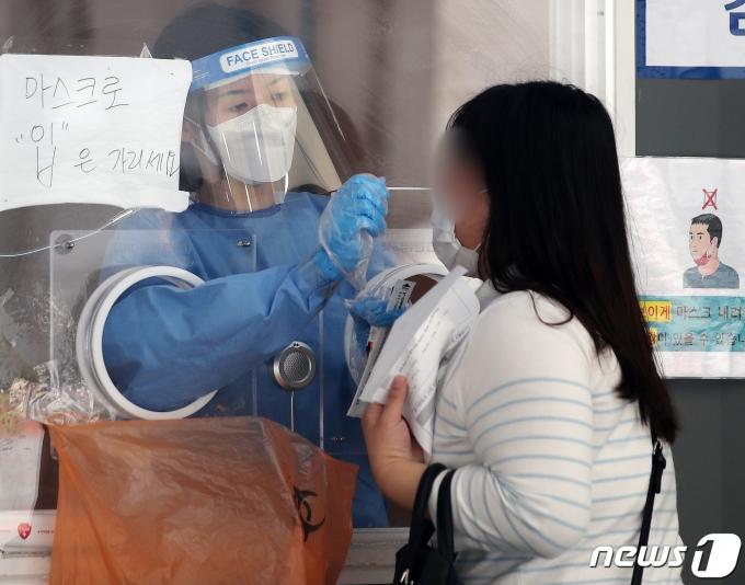 16일 오전 서울역에 마련된 중구임시선별진료소에서 의료진이 검체채취를 하고 있다. 2021.6.16/뉴스1 © News1 김진환 기자