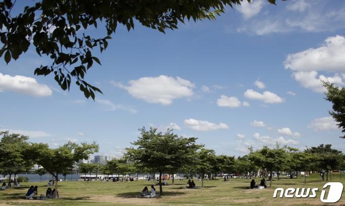 서울 낮 기온이 30도 안팎에 이르는 등 무더운 날씨를 보인 16일 서울 여의도 한강시민공원에서 시민들이 나무 밑에 앉아 휴식을 취하고 있다.. 2021.6.16/뉴스1 © News1 권현진 기자