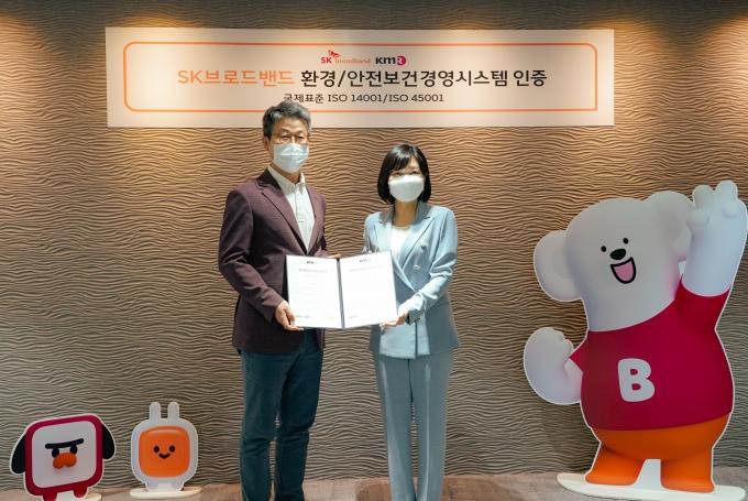 최진환 SK브로드밴드 대표(왼쪽)가 황은주 한국경영인증원장으로부터 ISO14001 및 ISO45001 인증서를 받는 모습. /사진제공=SKB