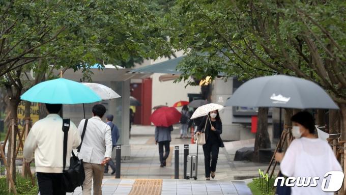 비가 내린 15일 오전 서울 세종로 광화문 네거리 인근에서 우산 쓴 시민들이 발걸음을 재촉하고 있다. 2021.6.15/뉴스1 © News1 김명섭 기자