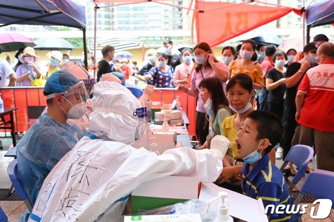 중국 남부 광둥성 성도 광저우시 한 체육관에 마련된 코로나19 선별진료소에서 2021년 5월 30일 거주자를 대상으로 대규모 코로나19 검진이 이뤄지는 모습. © 로이터=뉴스1