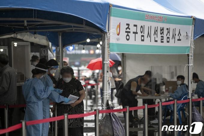 18일 오전 서울 중구 서울역광장에 마련된 신종 코로나바이러스 감염증(코로나19) 임시 선별검사소를 찾은 시민들이 안내를 받고 있다. 2021.6.18/뉴스1 © News1 이승배 기자