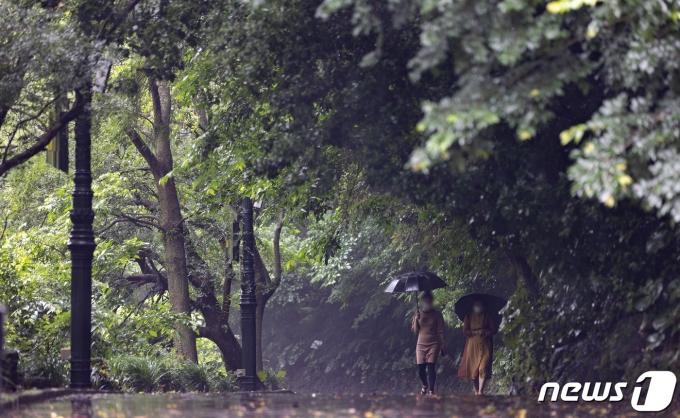 비가 내리는 15일 제주도 서귀포시 천지연폭포를 찾은 관광객들이 길을 거닐고 있다. 2021.6.15/뉴스1 © News1 이재명 기자