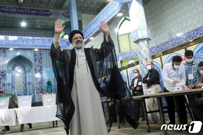 테헤란 시내의 한 투표소에서 18일 세예드 에브라힘 라이시 후보가 한 표를 행사한 뒤 손을 흔들어 보이고 있다. © 로이터=뉴스1