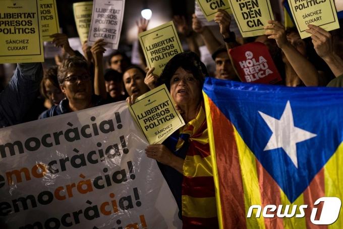 """2017년 10월 10일(현지시간) 카탈루냐 분리독립을 주장하는 주민들이 바르셀로나에서 카탈루냐 기와 """"정치범 석방하라"""" 고 쓴 플래카드를 들고 집회를 열고 있다. © AFP=뉴스1 © News1 우동명 기자"""