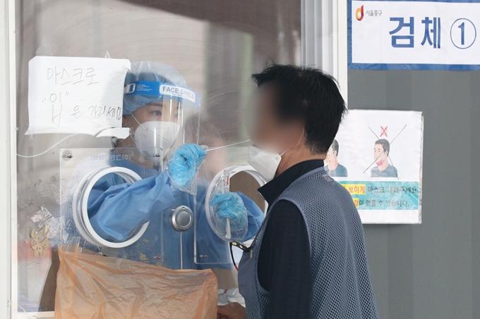 코로나19 일일 확진자 수가 22일 0시 기준 395명을 기록했다. 사진은 이날 오전 서울 중구 서울역광장에 마련된 임시선별진료소에서 검체검사를 받는 시민 모습. /사진=뉴스1