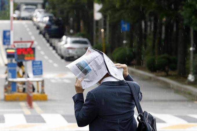 23일은 전국이 대체로 흐리고 소나기가 내릴 것으로 보인다. 사진은 22일 비가 내리는 서울 서초구 서울중앙지검 앞에서 한 시민이 신문지를 쓰고 이동하는 모습. /사진=뉴스1