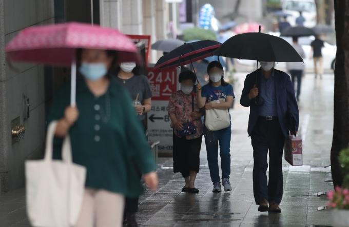 기상청에 따르면 24일은 전국이 흐리고 곳곳에 소나기가 내리겠다. 이날은 한낮기온 25도 안팎을 기록하며 다소 선선한 날씨를 보이겠다. 사진은 소나기가 내린 지난 22일 서울 강남구 역삼동 인근에서 시민들이 우산을 쓴 채 걷는 모습. /사진=뉴스1
