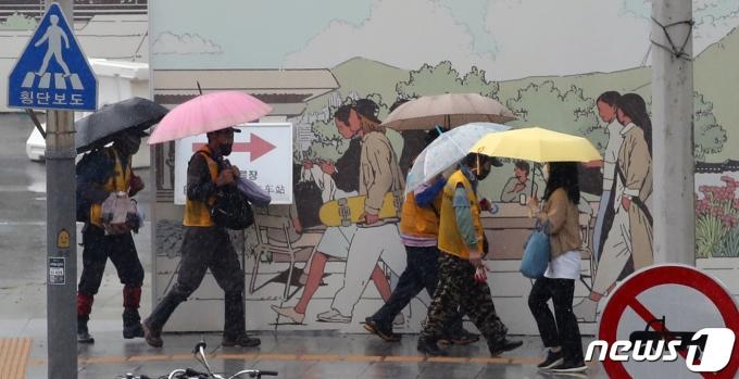 소나기가 쏟아진 23일 오후 서울 종로구 정부서울청사 인근 인도에서 시민들이 걸음을 재촉하고 있다. 2021.6.23/뉴스1 © News1 ,송원영 기자