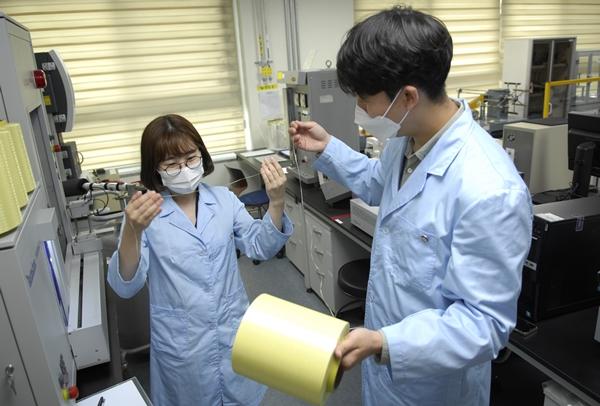 코오롱인더스트리는 2023년까지 아라미드 생산량을 약 두 배 늘릴 계획이다. 코오롱인더스트리의 연구원들이 아라미드 섬유인 헤라크론 제품을 살펴보는 모습. /사진=코오롱인더