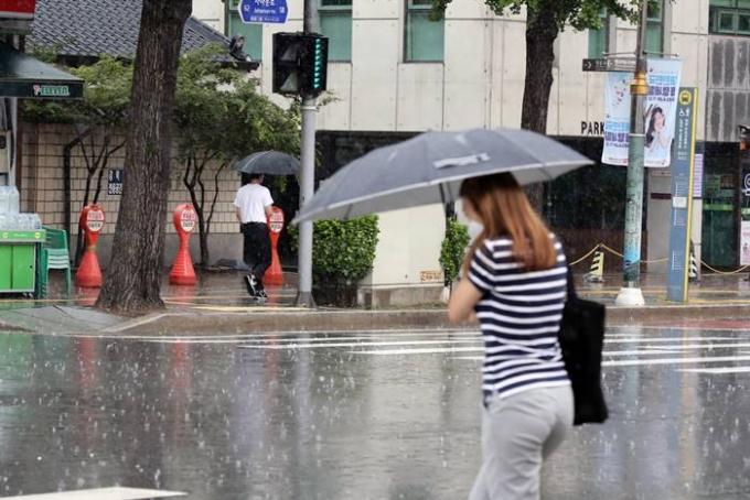 금요일(25일)에는 전국에 구름이 많고 낮부터 밤 사이 곳곳에 소나기가 내릴 것으로 전망된다. 사진은 지난 23일 서울 종로구 자하문로에서 우산을 쓴 시민이 발길을 재촉하는 모습. /사진=뉴스1