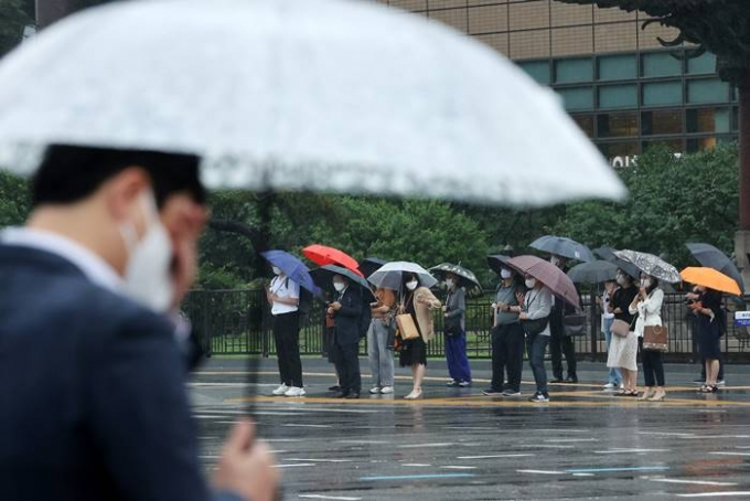 금요일(25일)은 전국에 구름이 많고 낮부터 밤 사이에 전국 곳곳에 소나기가 내린다. 사진은 지난 18일 서울 종로구 광화문네거리에서 우산을 쓴 채 출근하는 시민들의 모습. /사진=뉴스1