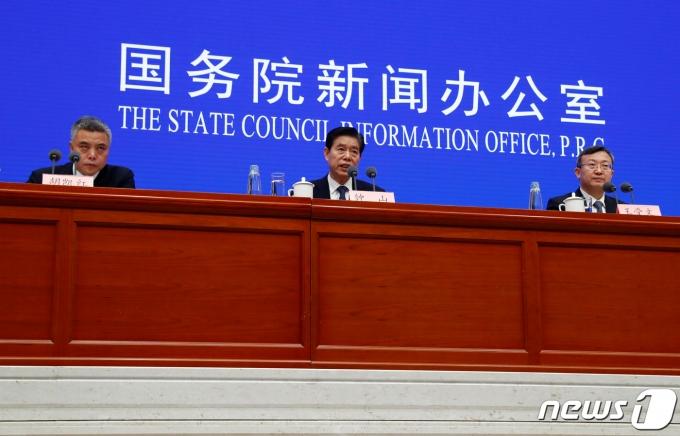 중산 중국 상무부장이 18일 (현지시간) 코로나19 팬데믹 이후 베이징 국무원 신문판공실에서 왕 셔우원 상무 부부장 등과 기자회견을 하고 있다. © 로이터=뉴스1 © News1 우동명 기자