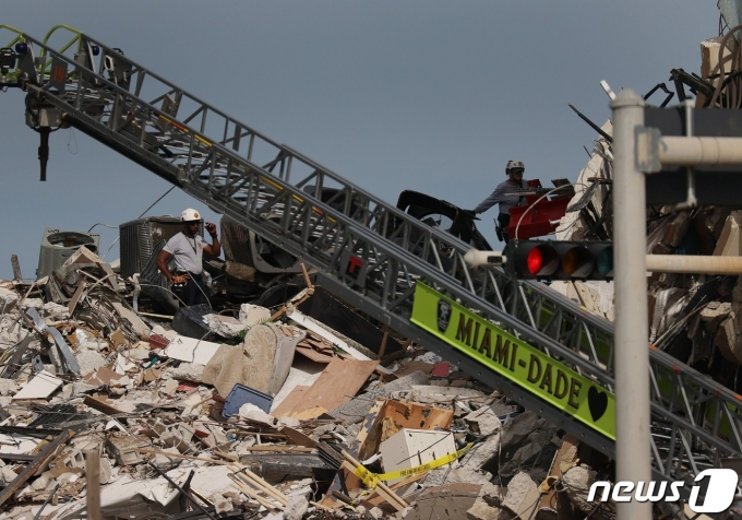 24일(현지시간) 플로리다주 마이애미의 서프사이드에 있는 12층 짜리 챔플레인 타워 콘도 건물이 폭격 맞은 듯 무너져 1명이 사망하고 99명이 실종된 현장서 구조대원들이 수색을 하고 있다. © AFP=뉴스1 © News1 우동명 기자