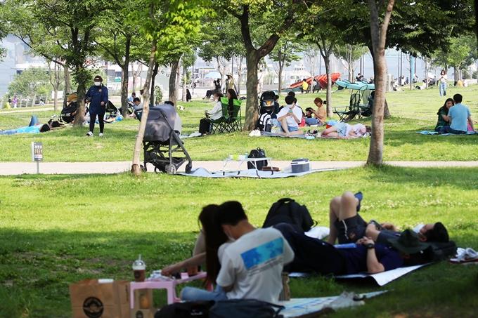 정부가 수도권에서 백신을 접종했어도 실외에서 마스크를 착용해야 한다는 방침을 내놨다. 사진은 지난달 20일 서울 영등포구 여의도한강공원에서 휴식을 취하는 시민들 모습. /사진=뉴스1