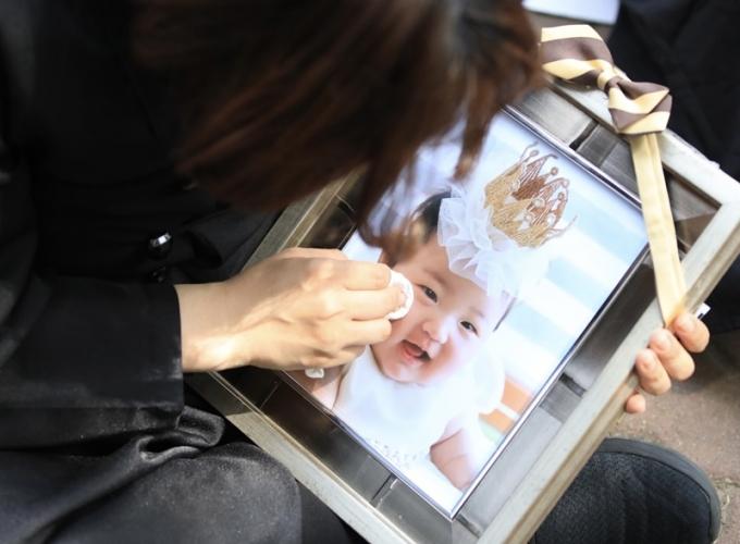 16개월 된 입양아를 학대해 숨지게 한 혐의를 받는 양부모의 항소심이 이번 달부터 시작된다. 사진은 지난 5월 1심이 진행되는 서울남부지방법원 앞에서 상복을 입은 한 시민이 정인이 사진을 닦고 있는 모습. /사진=뉴스1