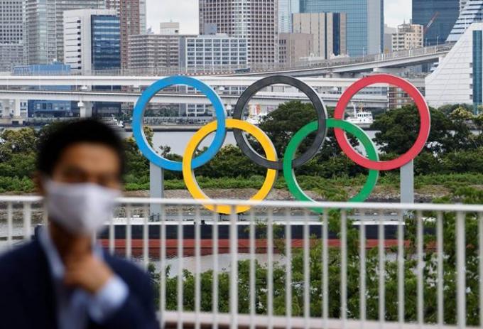 6일 타카타니 마사노리 일본 도쿄올림픽·패럴림픽 조직위원회 대변인은 지난 1일과 2일 각각 양성 판정을 받은 직원 2명이 선수촌 스태프라고 밝혔다. 사진은 지난달 27일 마스크를 쓴 채 도쿄올림픽 주경기장 조형물 앞을 지나가는 도쿄 시민의 모습. /사진=로이터