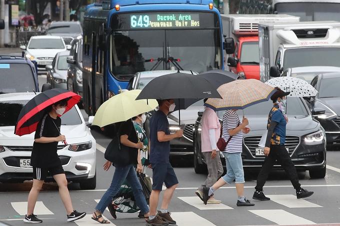 금요일은 전국에 천둥·번개를 동반한 소나기가 내리고 낮 기온은 32도 이상 오를 전망이다. 사진은 대구 도심 횡단보도에서 우산을 쓴 채 이동하는 시민들 모습. /사진=뉴스1