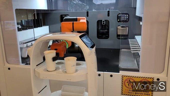 서울 마포구 상암동의 한 카페에서 로봇이 커피를 만든 뒤 서빙을 위한 로봇에 커피를 옮기고 있다./사진=머니S
