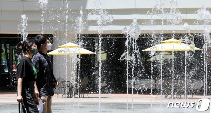 폭염특보가 내려진 23일 세종시 어진동에 위치한 한 쇼핑몰을 찾은 시민들이 바닥분수주위를 걸으며 더위를 식히고 있다. 2021.7.23/뉴스1 © News1 장수영 기자