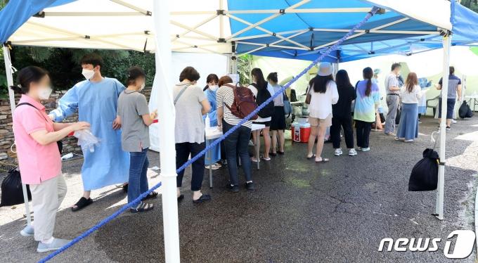 연일 무더위가 이어지고 있는 23일 서울 양천구 파리공원에 설치된 코로나19 찾아가는 선별진료소에서 시민들이 검사를 위해 순서를 기다리고 있다. 2021.7.23/뉴스1 © News1 이동해 기자