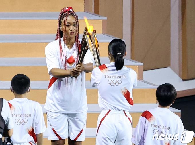23일 오후 일본 도쿄 국립경기장에서 열린 2020 도쿄올림픽 개막식에서 일본 테니스 선수인 오사카 나오미가 토치키스를 하고 있다.  2021.7.23/뉴스1 © News1 이재명 기자