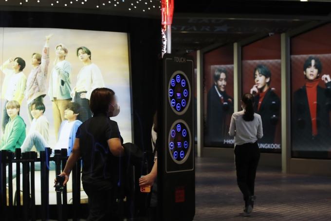20일 서울 중구 롯데면세점에 마련된 BTS의 광고판 앞을 시민들이 지나가고 있다./사진=뉴스1