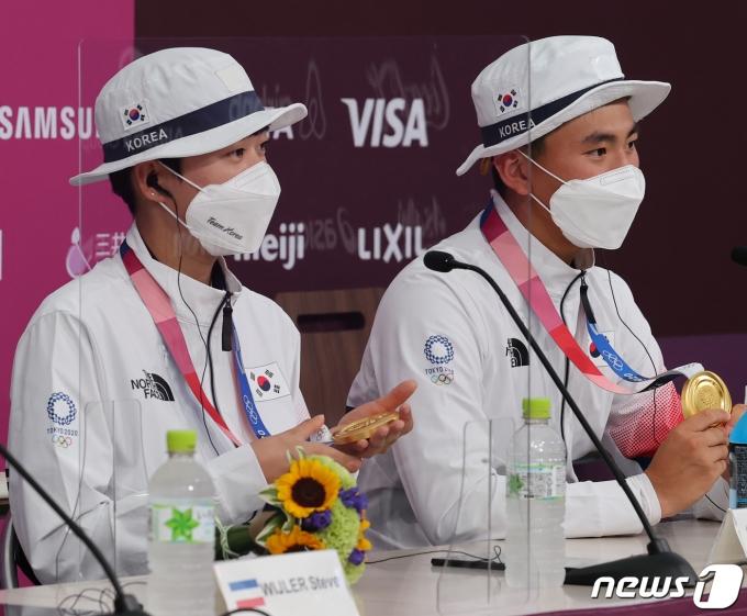 [사진] 금메달 만지는 양궁 듀오 안산과 김제덕