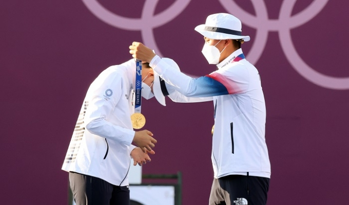 김제덕(오른쪽)이 24일 오후 일본 도쿄 유메노시마 양궁장에서 열린 2020 도쿄 올림픽 양궁 혼성전에서 금메달을 획득한 후 안산에게 금메달을 걸어주며 함께 기쁨을 누리고 있다. /사진=뉴시스