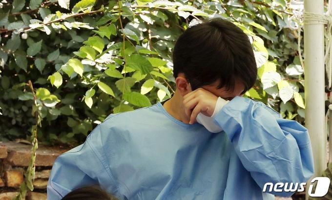 연일 무더위가 이어지고 있는 지난 23일 서울 양천구 파리공원에 설치된 코로나19 찾아가는 선별진료소에서 의료진이 땀을 닦고 있다./뉴스1 © News1 이동해 기자
