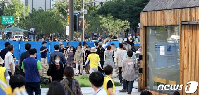 서울시가 광화문광장에 설치된 '세월호 기억공간' 철거를 위해 공간 안에 있는 사진과 물품 정리에 나서겠다고 통보한 23일 오후 물품정리를 반대하는 시민들이 광화문광장으로 도착하고 있다. 2021.7.23/뉴스1 © News1 박지혜 기자
