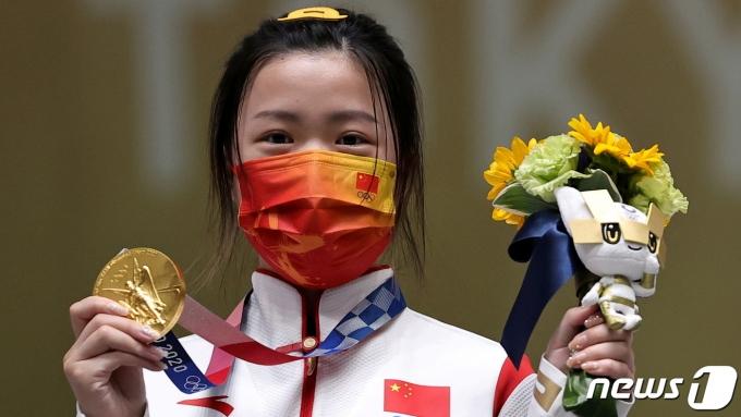 도쿄 올림픽 첫 금메달리스트인 중국의 사격 선수 양치엔이 금메달을 들어 보이고 있다. © 로이터=뉴스1 © News1 박형기