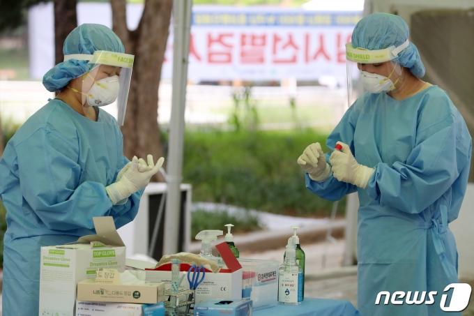 폭염이 이어진 지난 23일 오후 대구 달서구 두류야구장 임시선별검사소에서 의료진이 코로나19 진단검사를 이어가고 있다./뉴스1 © News1 공정식 기자