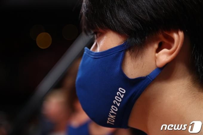 7월 25일 2020 도쿄올림픽이 대회 3일 차를 맞은 가운데, 대회 관계자가 '도쿄 2020' 문구가 적힌 마스크를 착용하고 있다. © 로이터=뉴스1 © News1 정윤영 기자