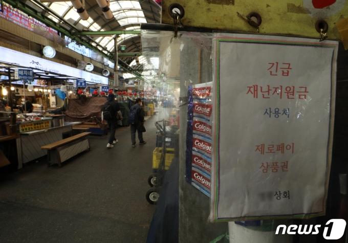 서울 광장시장의 한 매장에 재난지원금 결제가 가능하다는 안내문이 붙어 있다. 2021.7.25/뉴스1 © News1 신웅수 기자