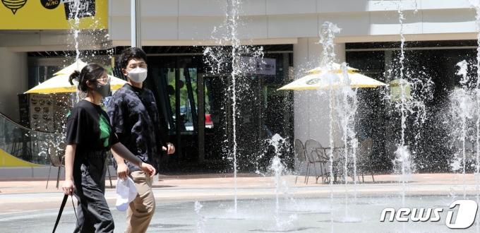 세종시에서 낮 최고기온 35℃와 체감온도 37℃를 기록하며 폭염특보가 내려진 23일 세종시 어진동에 위치한 한 쇼핑몰을 찾은 시민들이 바닥분수주위를 걸으며 더위를 식히고 있다. 2021.7.23/뉴스1 © News1 장수영 기자